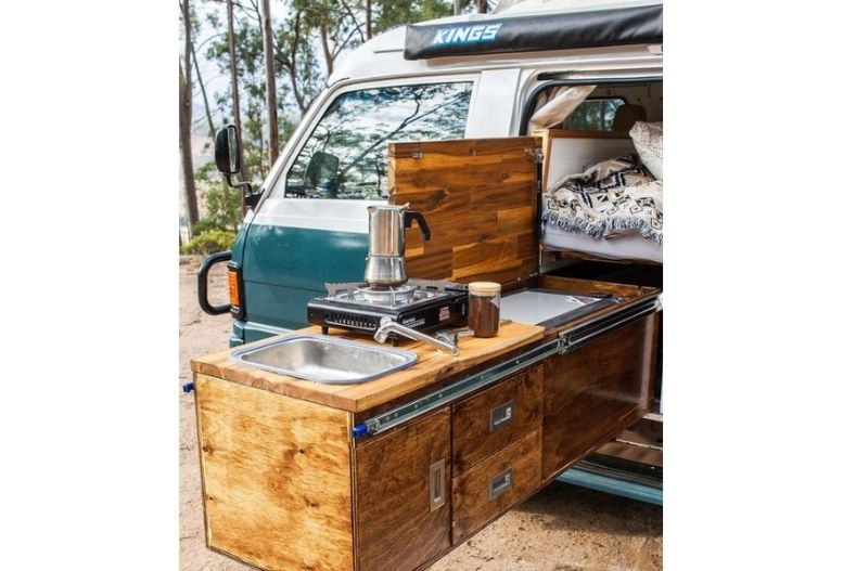 Wooden kitchen cabinets with built in cooler, sink and single burner built to slide in and out of camper van.