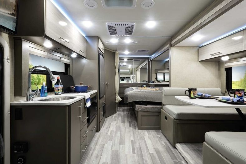 Thor Gemini Best Class B plus RV interior with grey laminate wood flooring and tan accents, dinette on right, bed in back and kitchenette on left