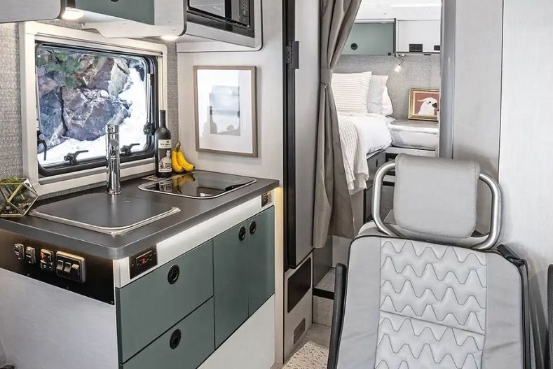 Winnebago interior view with small kitchenette on left, bucket seats on right facing front of vehicle and partial view of curtained bedroom in rear