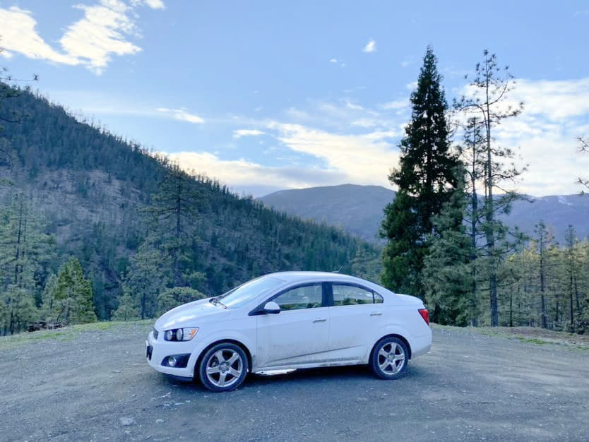 White Chevy Sonic car camper parked on an overlook
