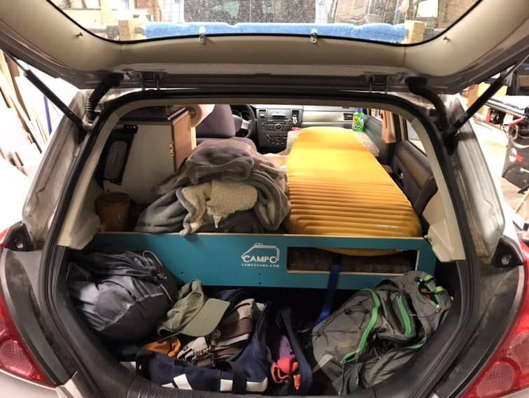 The back hatch open showing the inside contents of a Nissan Versa car camper