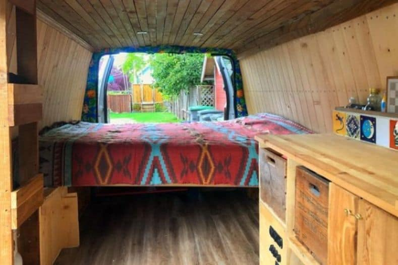 The Palm Van interior has natural wood paneling on the sides and roof, handmade wooden cabinets and cubbies and a bed spanning the width of the van.