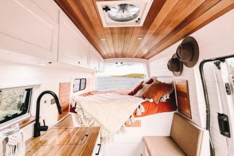 Vendy and Marz's Ford Transit cargo van conversion interior with wood paneling and rusty orange accents