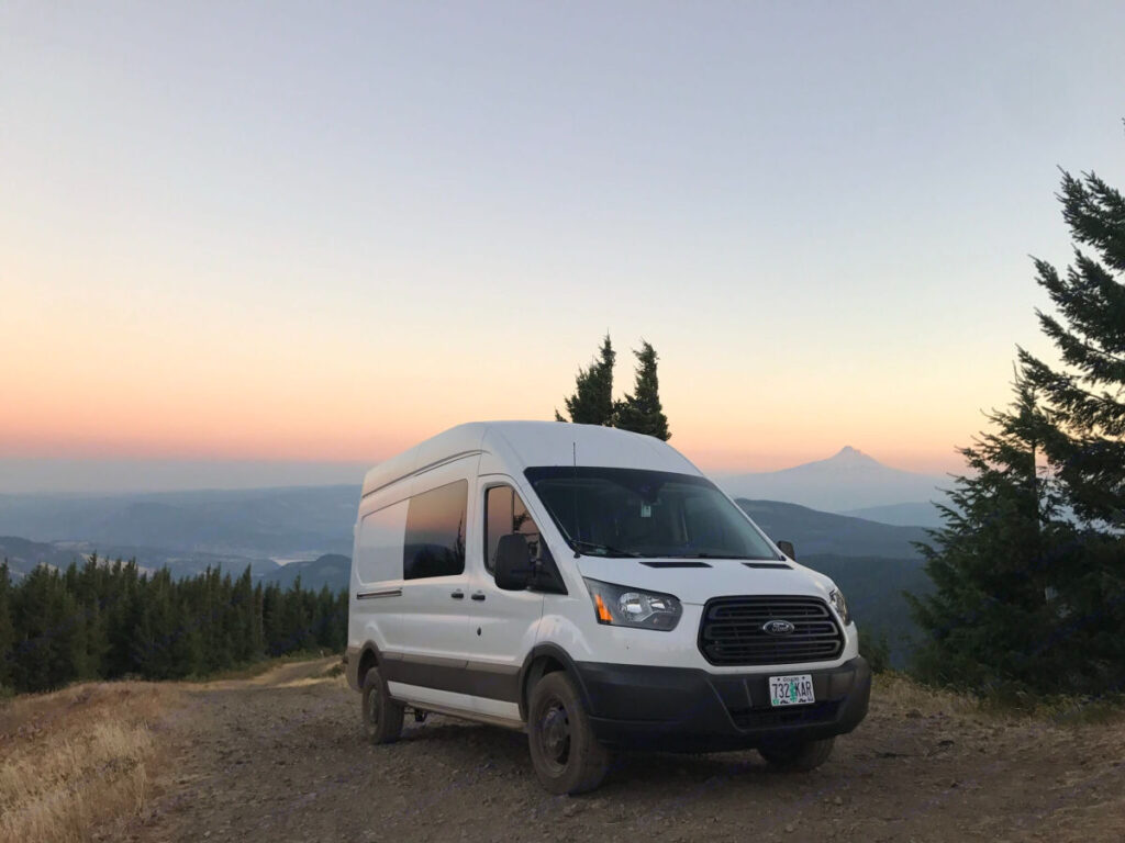 Ford Transit stealth camping van parked on a hill in Oregon