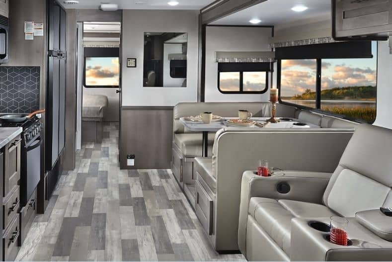 Interior view of Forest River FR3 32DS Motorhome with neutral tones, dinette, stove, fridge and recliners shown with bedroom in background