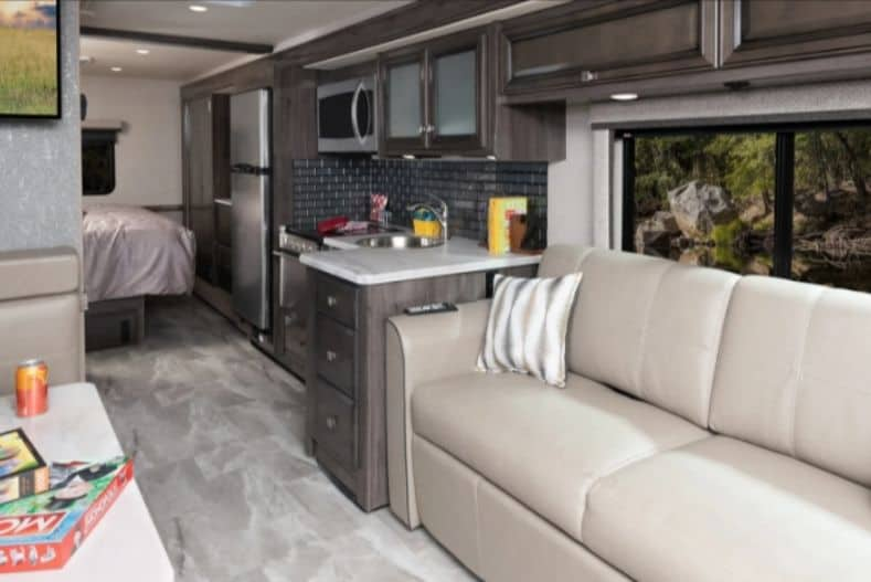 Holiday Rambler Admiral 34J Interior view with master bed open to the kitchen, sofa in forefront