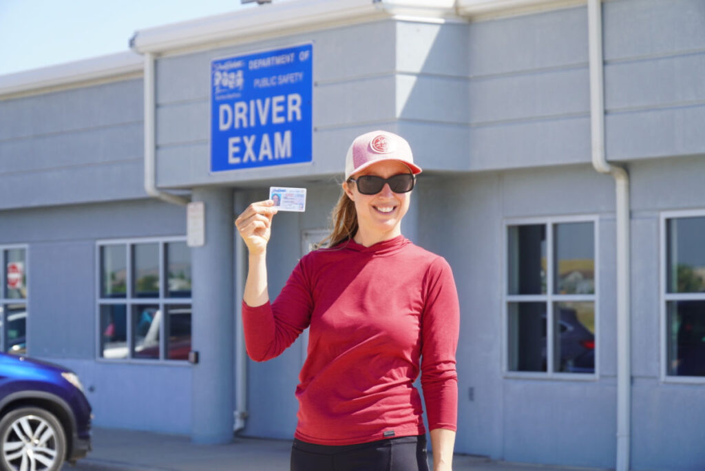Woman stands in front of a DMV holding her South Dakota driver's license
