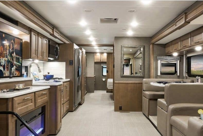 Thor Motor Coach Challenger 37DS Class A motorhome with bunks interior view with brown, beige and natural wood tones. Dinette and recliners partially show to the right of frame, kitchenette to the left and bedroom and bathroom hidden near the rear