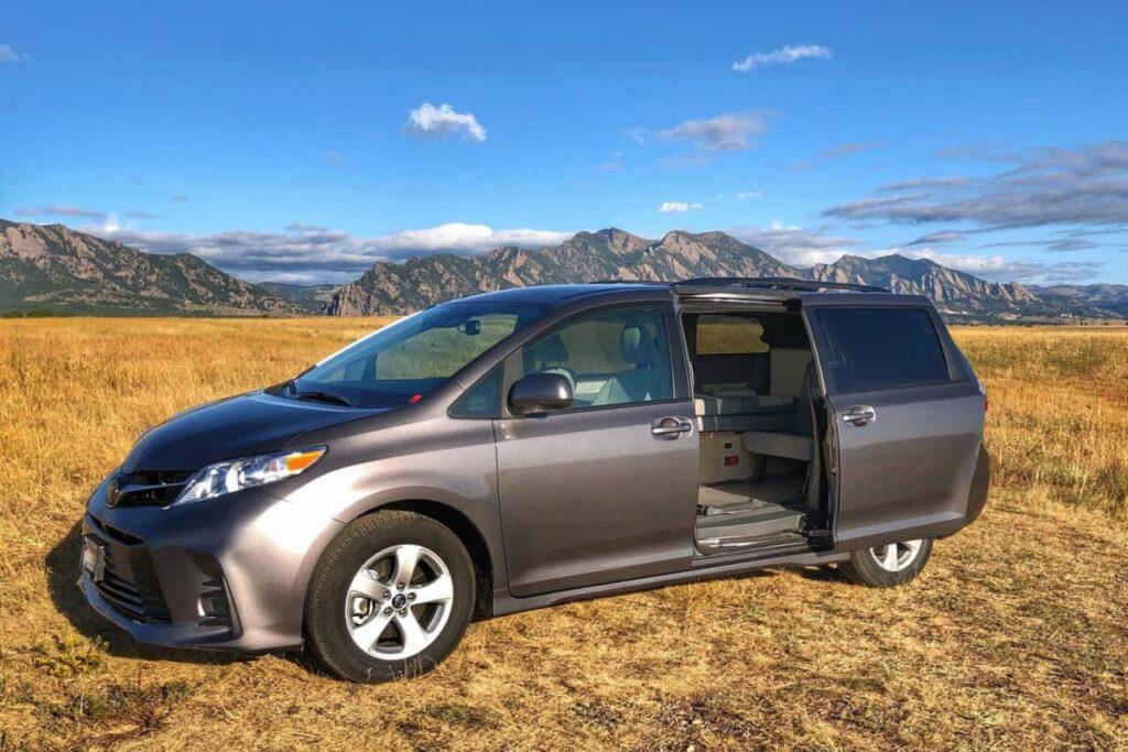 Toyota Sienna minivan stealth camper parked in a field