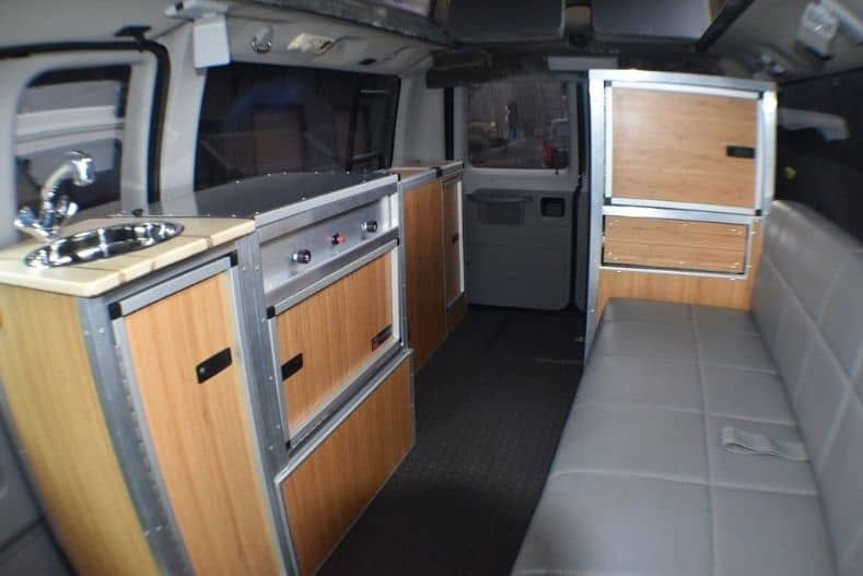 Trail Kitchens kitchen kit with wood panels and steel hardware in a cargo van conversion