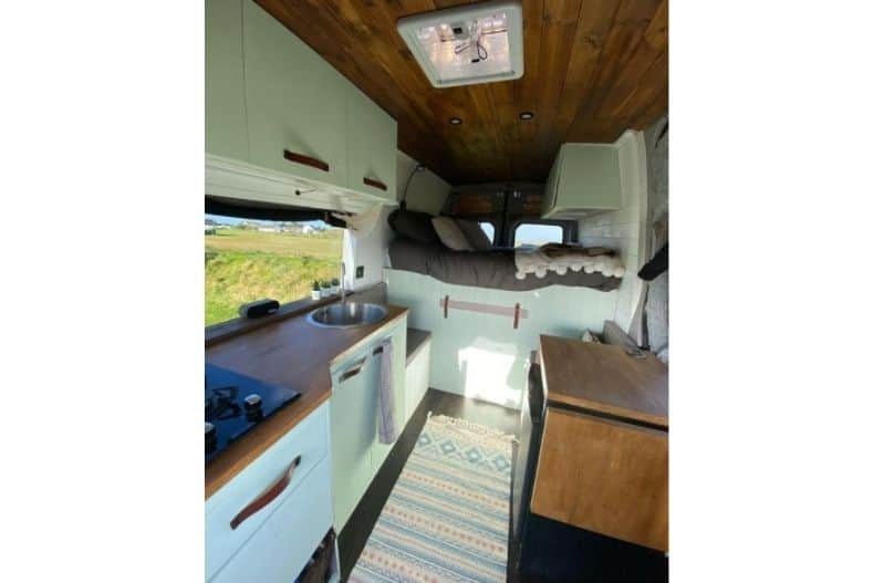 VW Crafter conversion interior with pale green cabinets, wood paneling, kitchenette and bed
