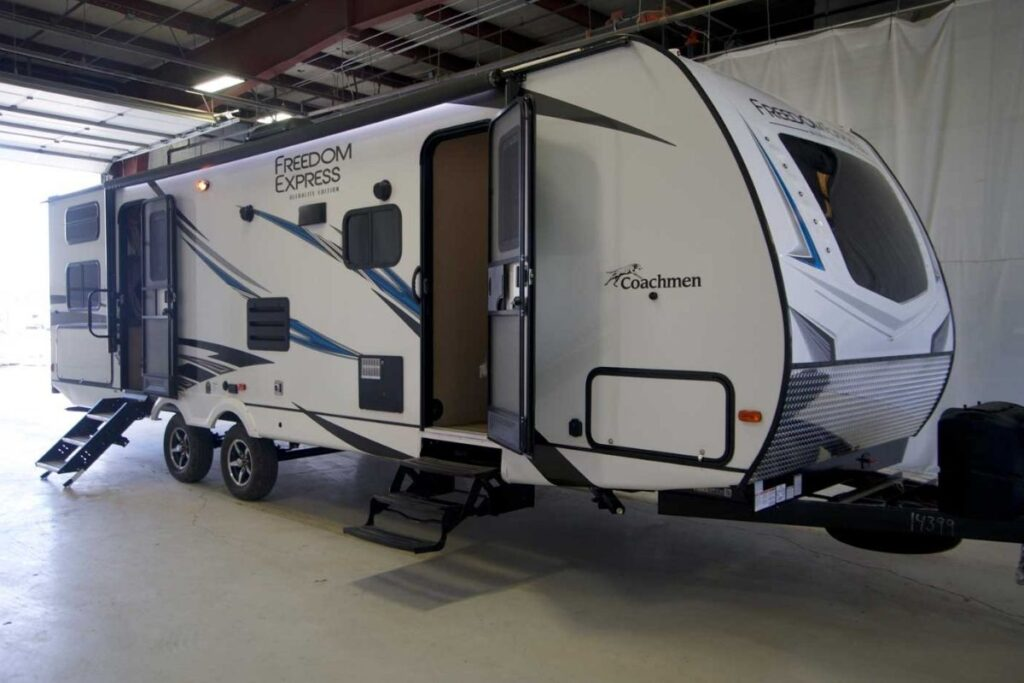 Coachmen Freedom Express travel trailer exterior, white with blue and black accents, shown in a garage