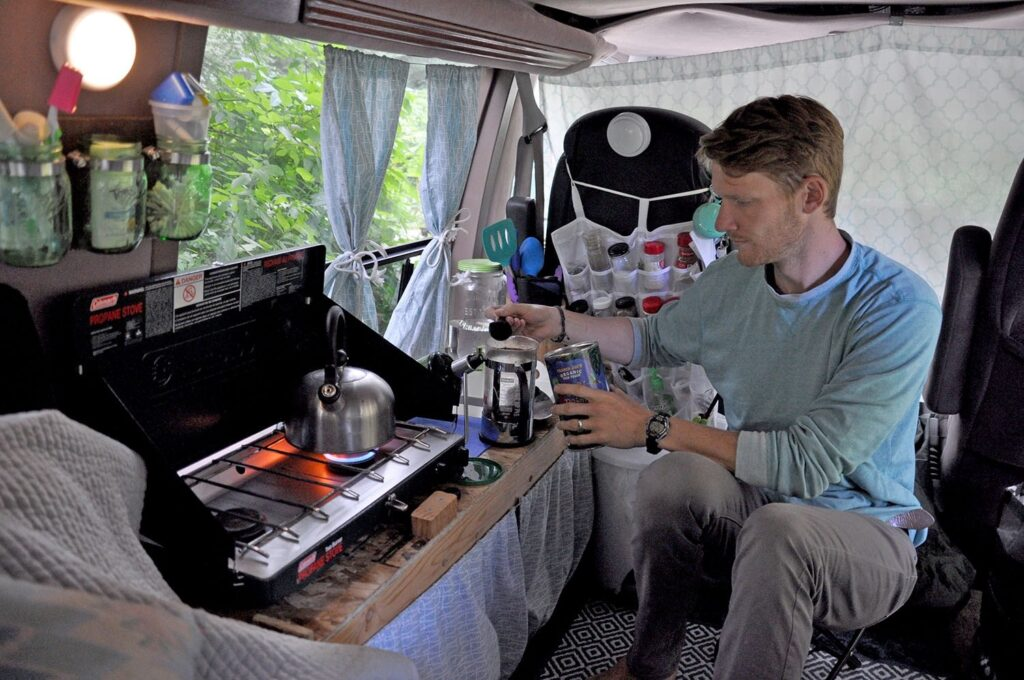 Man cooking at his super simple van kitchen unit