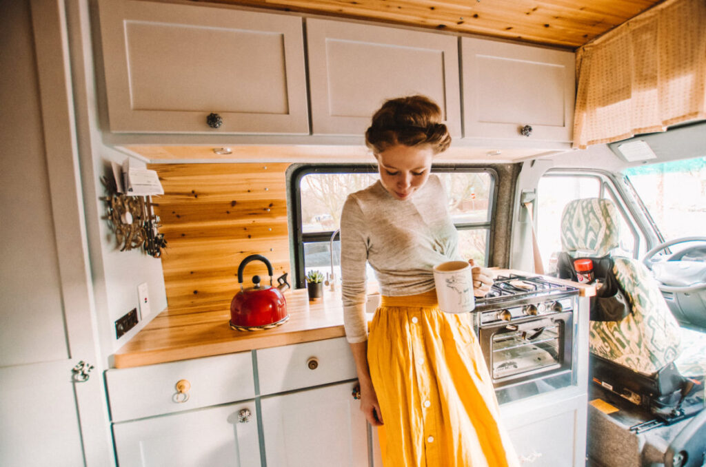 Woman standing in front of her campervan kitchen