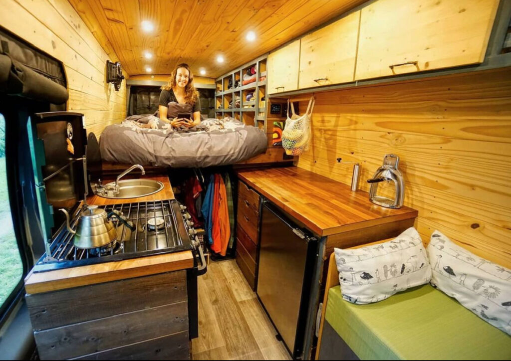 Woman sitting in a bed way behind her van kitchenette
